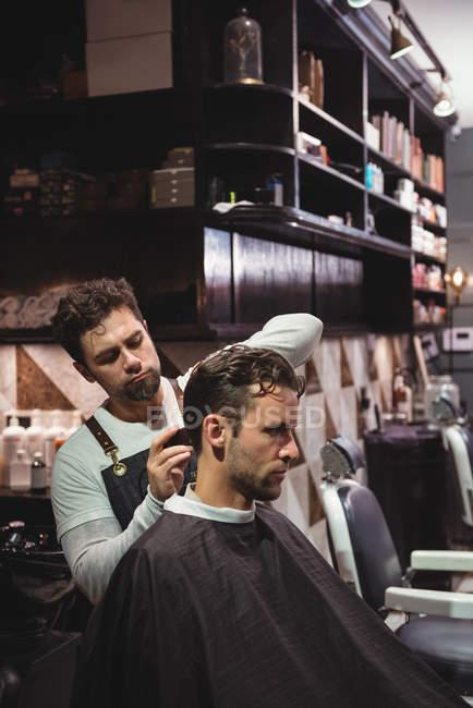 Peluquería masculina que corta el cabello del cliente con trimmer en la barbería - foto de stock