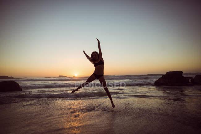 Женщина прыгает на пляже во время заката — стоковое фото