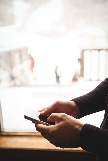 Man on his phone in front of window at a ski resort — Stock Photo
