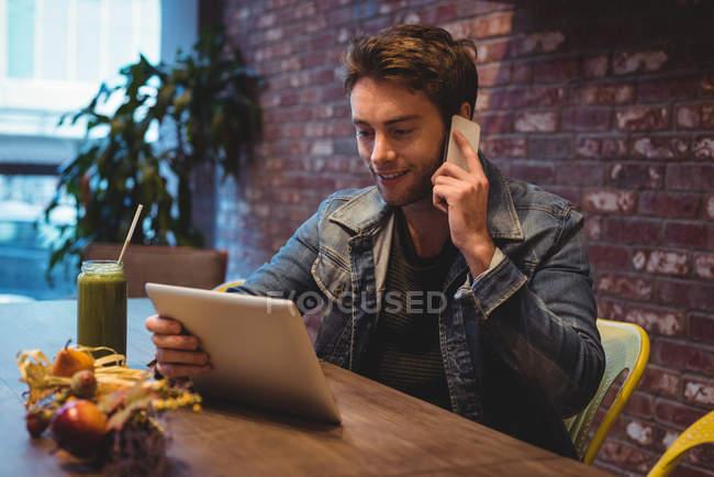 Mann telefoniert im Café mit digitalem Tablet — Stockfoto