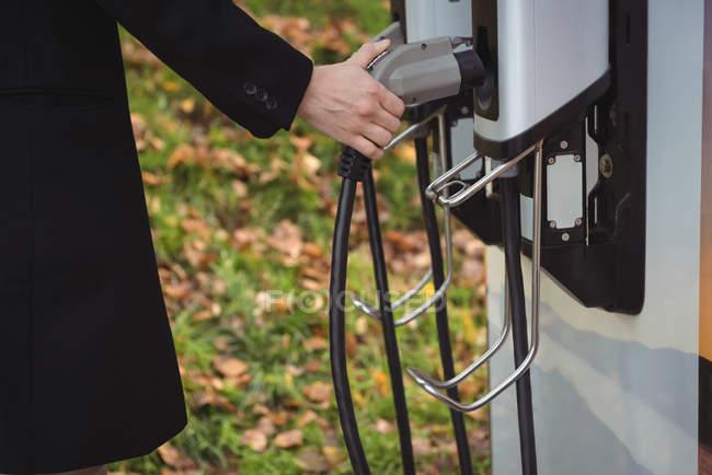 Partie médiane de l'homme tenant le chargeur de voiture à la station de recharge du véhicule électrique — Photo de stock