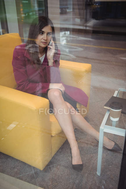 Businesswoman talking on mobile phone in office — Stock Photo