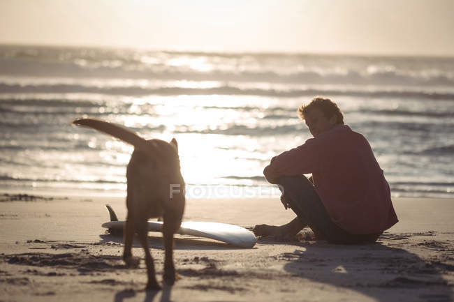 Man with surfboard sitting on beach at dusk with his dog — Stock Photo
