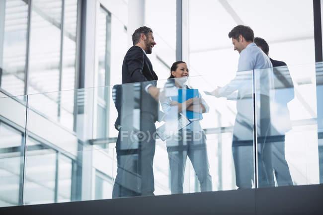 Gruppe von Geschäftsleuten interagiert im Flur eines Bürogebäudes — Stockfoto