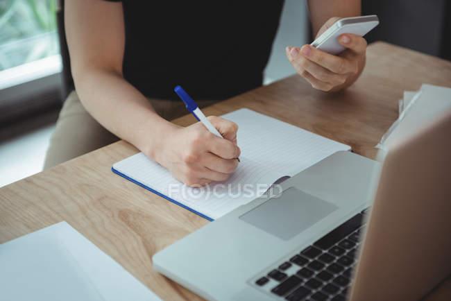 Виконавчим бізнесу писати на щоденник під час використання мобільного телефону в офісі — стокове фото