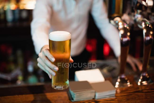 Бармен, яка виступає з келихом пива на зустрічну в бар — стокове фото