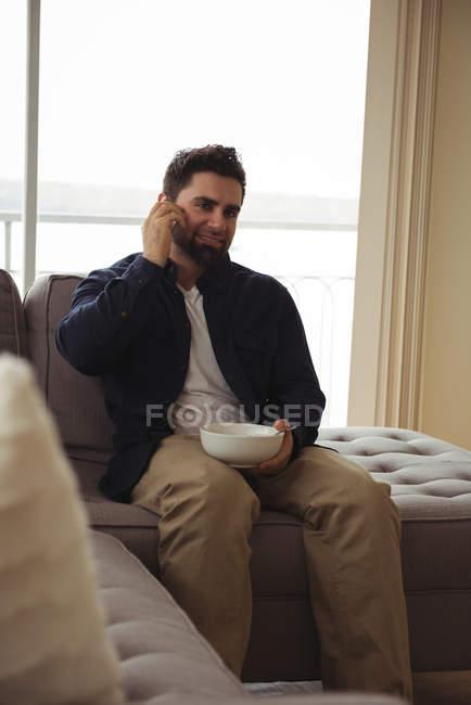 Homem falando no celular enquanto toma café da manhã no sofá — Fotografia de Stock