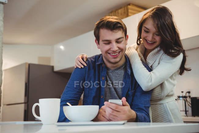 Casal usando telefone celular enquanto toma café da manhã na cozinha em casa — Fotografia de Stock