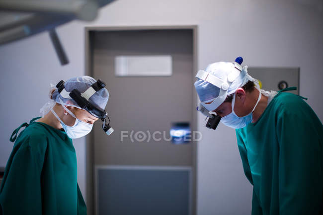 Chirurgen tragen Operationslupen während der Operation im Operationssaal — Stockfoto