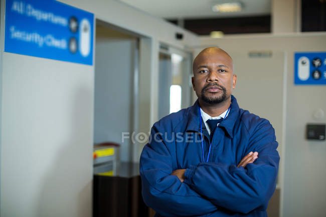 Portrait of airport security officer standing with arms crossed in airport terminal — Stock Photo