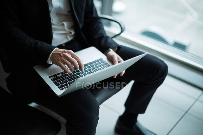 Businessman using laptop in waiting area at airport terminal — Stock Photo