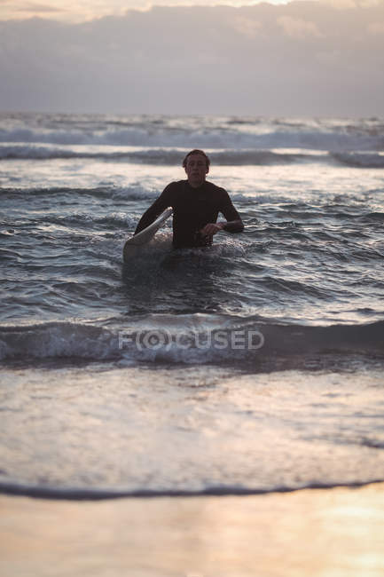 Portrait of a man carrying surfboard coming out of sea at dusk — Stockfoto