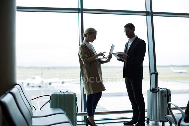 Business people using mobile phone and digital tablet at airport — Stock Photo