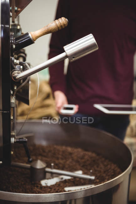 Mid-section of man holding smartphone and digital tablet besides coffee grinding machine — Stock Photo