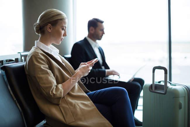 Femme utilisant un téléphone portable dans la salle d'attente au terminal de l'aéroport — Photo de stock