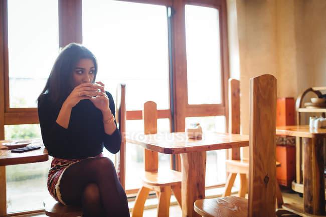 Bella donna che prende una tazza di caffè nel caffè — Foto stock