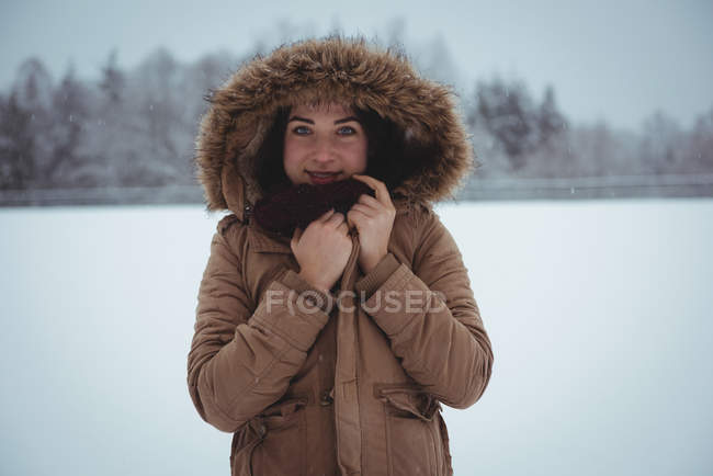 Портрет улыбающейся женщины в меховой куртке, наслаждающейся снегопадом зимой — стоковое фото