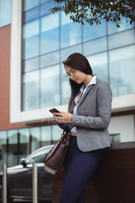 Testo donna d'affari di messaggistica sul cellulare mentre levandosi in piedi presso city street — Foto stock