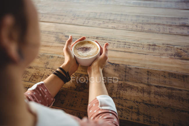 Close-up of woman holding coffee cup in cafe — Stock Photo