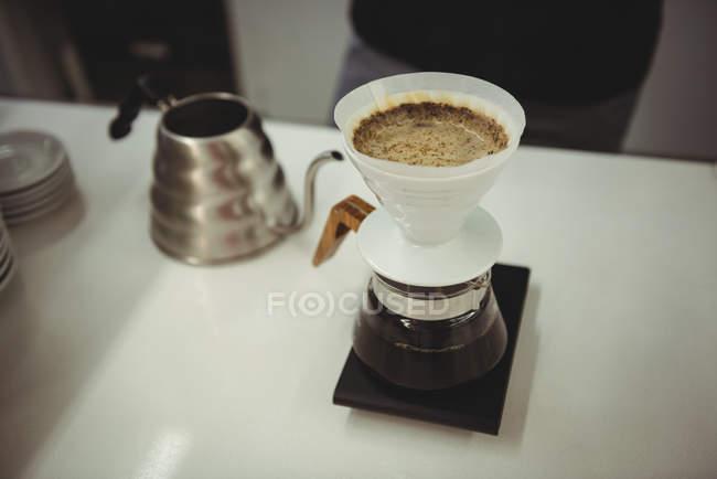 Filtro de café funil e panela de água quente na mesa no café — Fotografia de Stock