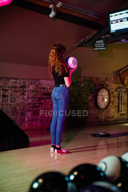 Mujer joven sosteniendo una bola de bolos en la bolera - foto de stock
