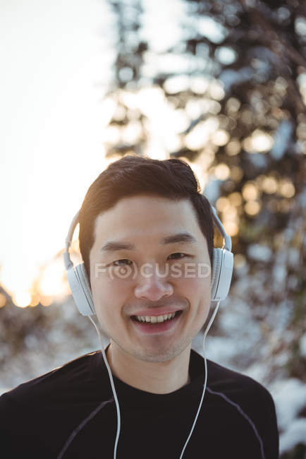 Portrait of man listening to music in headphones during winter — Stock Photo
