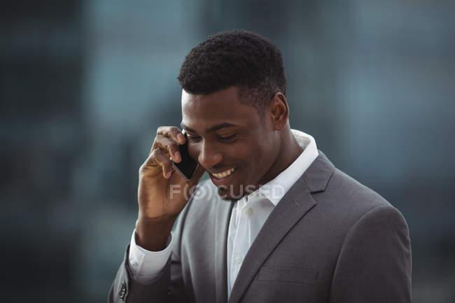 Бизнесмен разговаривает по мобильному телефону на офисной террасе — стоковое фото