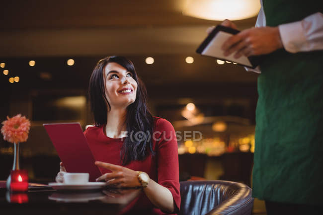 Waiter taking order from woman in a restaurant — Stock Photo