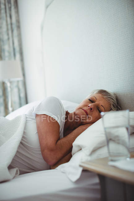 Senior woman resting on bed in bedroom at home — Stock Photo