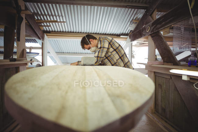 Man making surfboard in workshop interior — стоковое фото