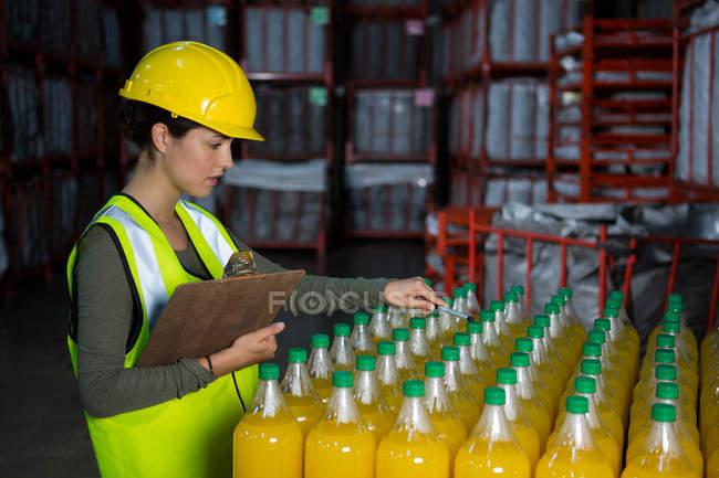 Женщина-работница осматривает соковые бутылки на заводе — стоковое фото