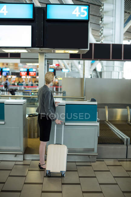 Rear view of businesswoman standing at a check-in counter with luggage in airport terminal — Stock Photo