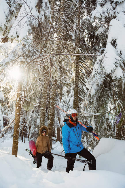 Couple with ski and snowboard walking on snowy mountain slope — Stock Photo