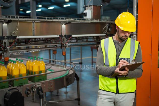 Серьезный работник мужского пола пишет на планшете на соковом заводе — стоковое фото