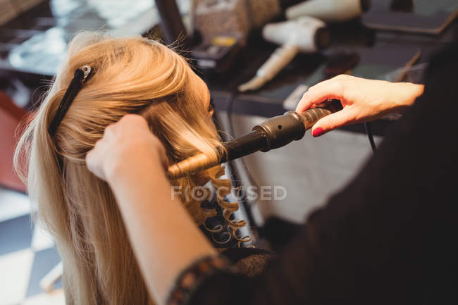 Крупный женский парикмахер, укладка волос клиентов в салоне — стоковое фото