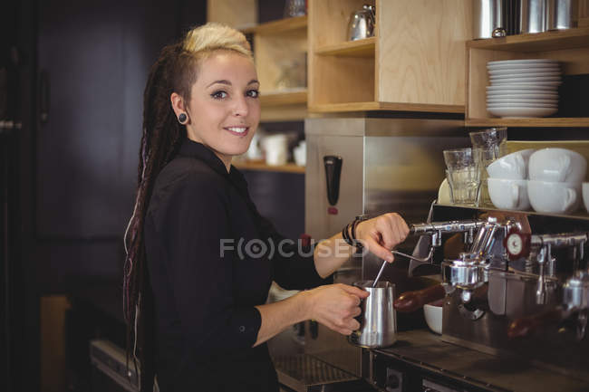 Portrait of smiling waitress using the coffee machine in cafe — Stock Photo