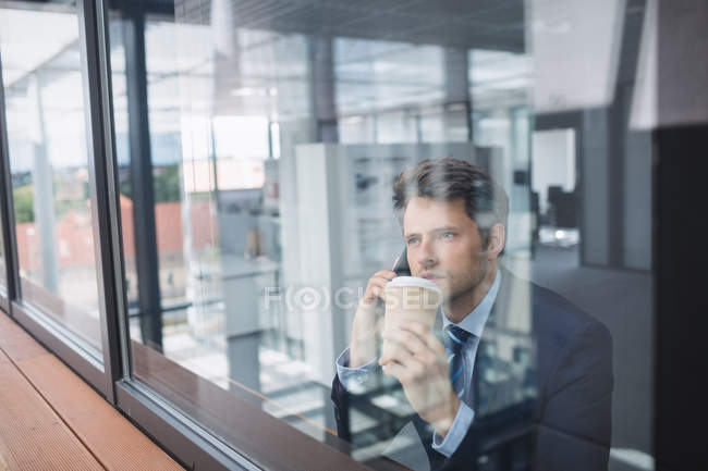 Businessman using mobile phone and holding disposable coffee cup in office — Stock Photo