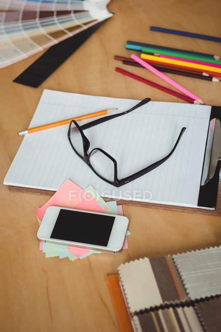 Teléfono móvil con portapapeles, gafas, lápices y papelitos en la mesa en la oficina - foto de stock
