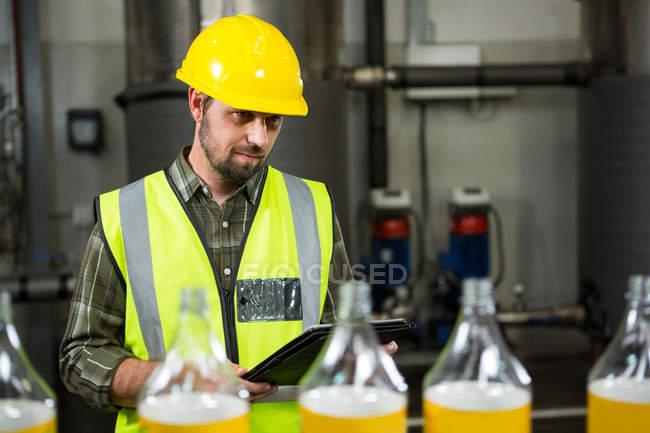Задумчивый работник мужского пола с цифровыми таблетками на соковом заводе — стоковое фото