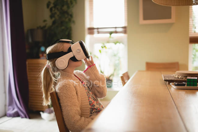 Girl sitting at table and using virtual realty headset at home — Stock Photo