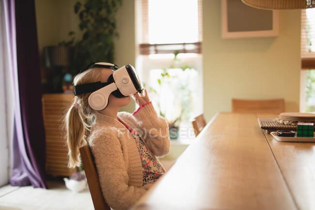 Fille assise à la table et en utilisant un casque de réalité virtuelle à la maison — Photo de stock