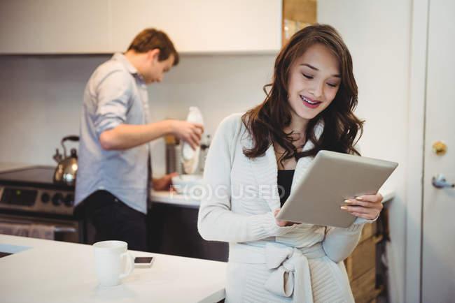 Femme utilisant tablette numérique tandis que l'homme travaillant en arrière-plan à la cuisine — Photo de stock