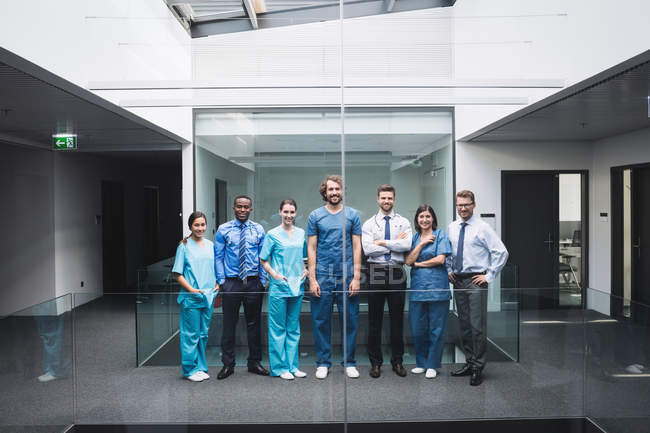 Retrato de sonriente médicos de pie juntos en el pasillo del hospital - foto de stock