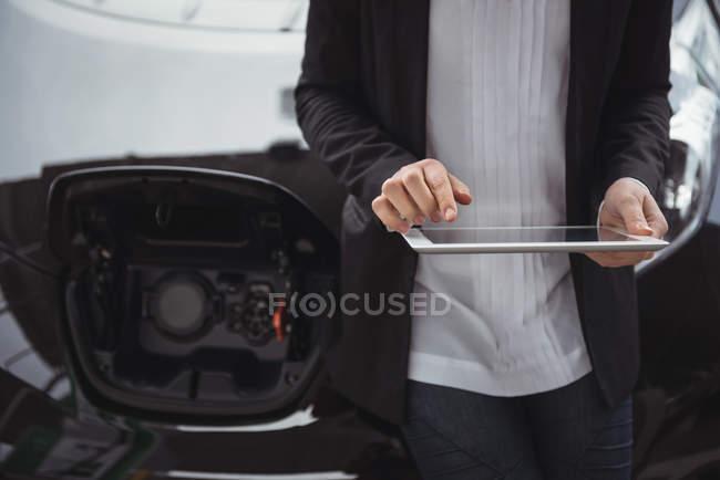 Section médiane de la femme debout à côté de la voiture électrique et à l'aide de tablette numérique — Photo de stock
