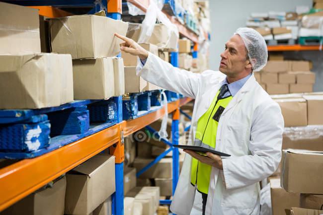 Technicien tenant un dossier sur tablette numérique à l'usine de viande — Photo de stock