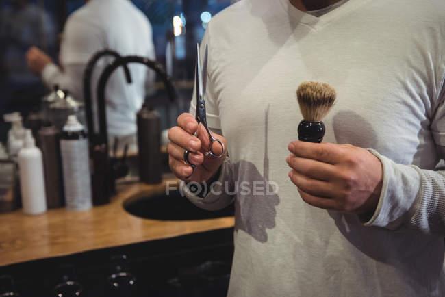 Metà sezione di mani barbiere che tengono forbici e pennello da barba nel negozio di barbiere — Foto stock