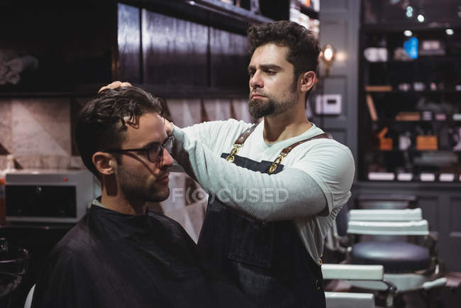 Barber styling client hair in barbershop — Stock Photo