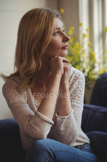 Thoughtful woman sitting on sofa in living room at home — Stock Photo