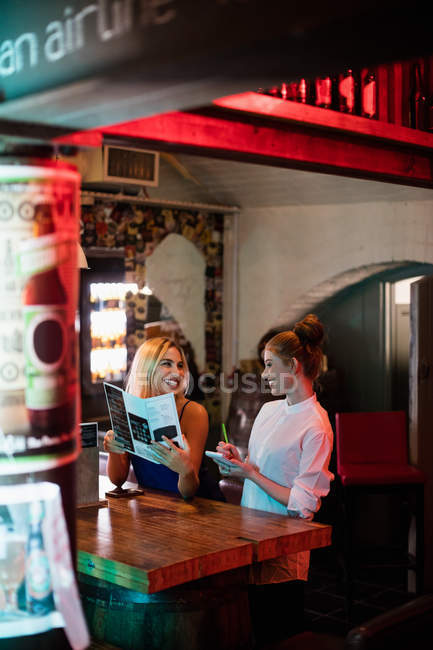 Waitress discussing the menu with the customer in the bar — Stock Photo
