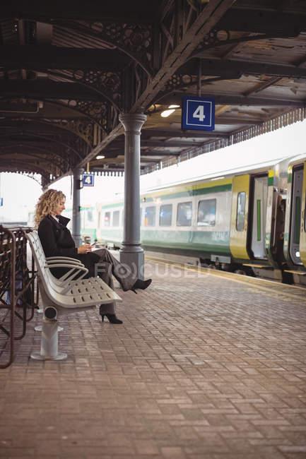 Вид сбоку на предпринимательницу, ожидающую поезда на скамейке — стоковое фото